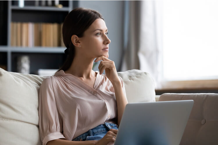 young woman sitting on couch with laptop in front of her, thinking