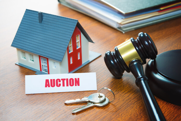 gavel on desk, next to home keys and an auction note