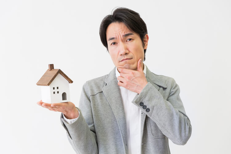 man thinking while holding a home miniature replica