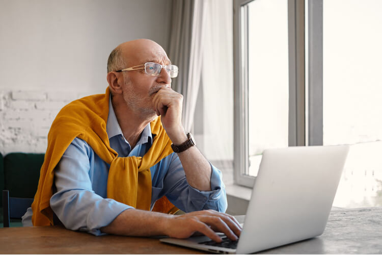 Pensive old man in front of laptop